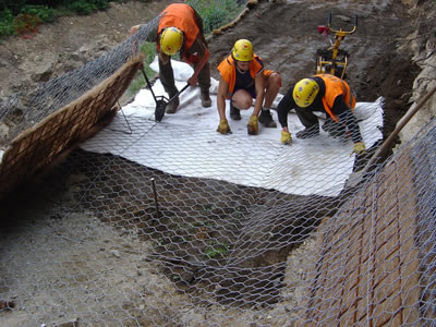 Three workers are layering green terramesh onto ground, stabilize it by reinforcing wire and rings.